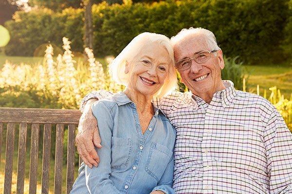 Elder Law concept: Couple sitting on park bench