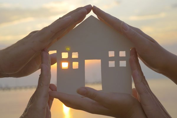 Estate planning concept: hands holding a cardboard cutout of house
