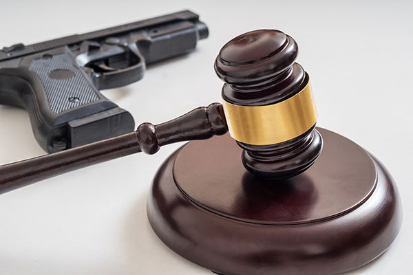 Gavel in front of a pistol. Gun laws and legislation concept.